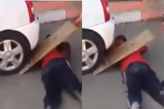 مخاطرًا بحياته.. بالفيديو: شاب يتحدي بمرور مركبة من فوقه