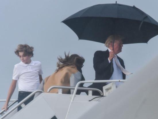 """ترامب يتمسك بالمظلة لحماية تسريحة شعره ويترك زوجته وابنه تحت المطر! """"صور """""""