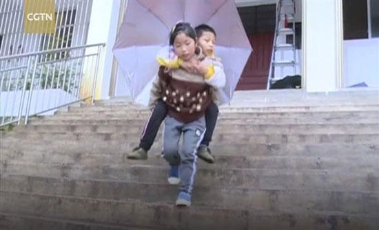 طفلة 9 سنوات تحمل شقيقها المعاق يوميًا لتوصيله إلى مدرسته..شاهد