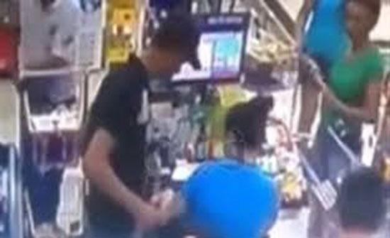 لص يهدد عاملة كاشير بسكين أمام الزبائن (فيديو)