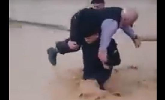 بالفيديو : رجل أمن يحمل مسناً على ظهره حاصرته مياه الامطار في اربد