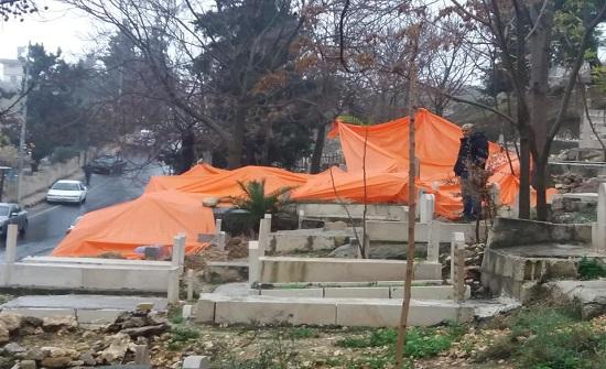"""بالصور : بعد انهيار سور"""" العيزرية"""" .. تغطية القبور بغطاء بلاستيكي"""