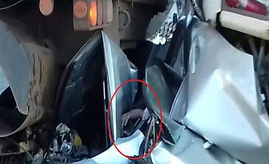 علقت سيارته أسفل شاحنتين.. هكاذ نجا من الموت بأعجوبة (صور)