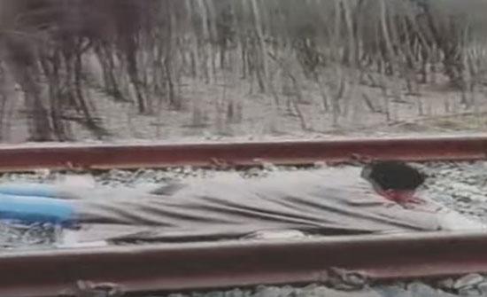 شاب يتحدى الموت مستلقيا على قضبان أثناء عبور قطار مسرع (فيديو)