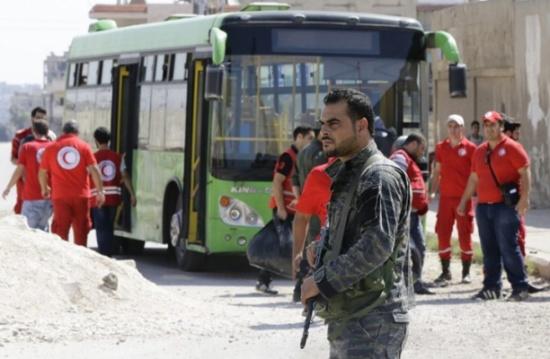 بدء خروج مقاتلين سوريين وعائلاتهم من حي الوعر بموجب اتفاق مع الحكومة