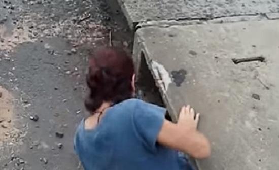 امرأة تتسلل لبالوعة صرف مياه لإنقاذ قطة (فيديو)