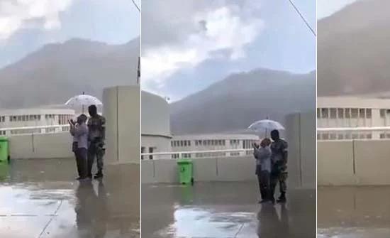 شاهد: رجل أمن يحمل مظلة لأحد الحجاج أثناء قيامه بالدعاء لحمايته من المطر