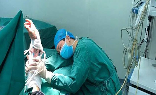 بالصورة : أجرى 6 عمليات متواصلة.. صورة مؤثرة لجراح متفان نام حاملا ذراع مريضه