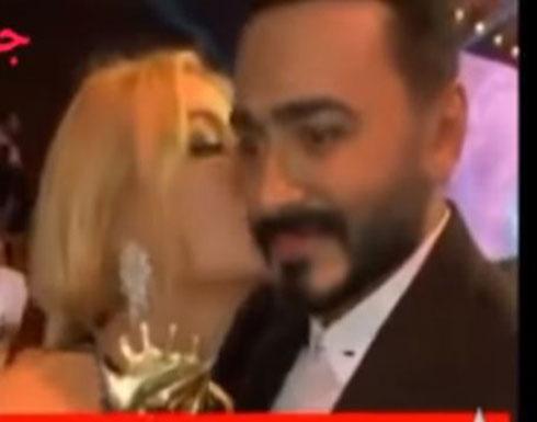بالفيديو : تامر بموقف محرج.. ممثلة شقراء طبعت قبلة ساخنة على خده!