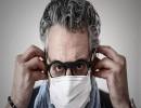 طبيب فرنسي يرتدي كمامة قبل معاينة احد مرضاه في عيادته في احدى ضواحي باريس