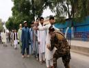 عنصر من الأمن الأفغاني يفتش الناخبين