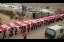 شاهد : طلاب في عرسال جالوا رافعين سلسلة من الأعلام اللبنانية على رؤوسهم