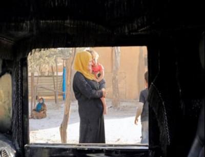 نساء وأطفال فارون من دير الزور في أحد المخيمات شمال الرقة