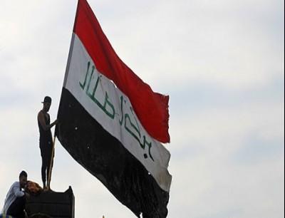 متظاهرون يرفعون علم العراق