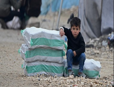 طفل يجلس جنب أكياس مساعدات في شمال سوريا (أرشيفية)