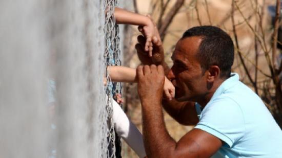 بعد عام من الفراق.. أسرة سورية تتبادل القبلات عبر سياج