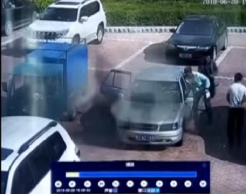 """بالفيديو: صيني """"يطفئ"""" سيارة مشتعلة بالنفخ عليها!"""