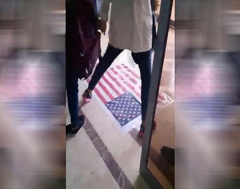 شاهد .. طلبة ايرانيون يرفضون السير على العلم الامريكي