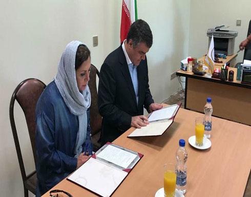 بالصور.. زوجة ماهر الأسد وهي توقع اتفاقية في إيران