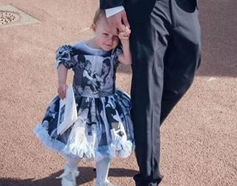 بالصور : طفلة ترتدي فستانا مغطى بصور شقيقها خلال جنازته