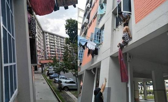 رجل يمسك امرأة من شعرها أثناء سقوطها من الطابق الثالث