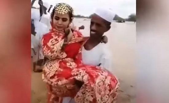 شاهد.. عريس سوداني يحمل عروسه فوق السيول
