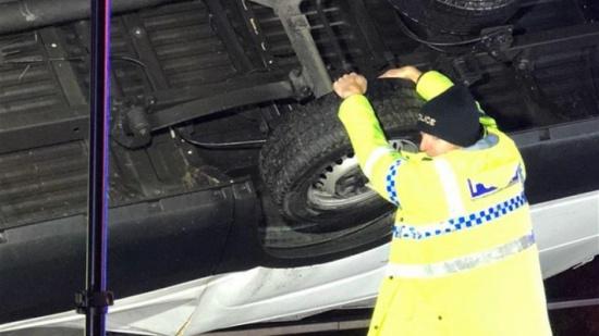 بالصور- شرطي ينقذ سيارة من الوقوع عن الجسر باستخدام يديه!
