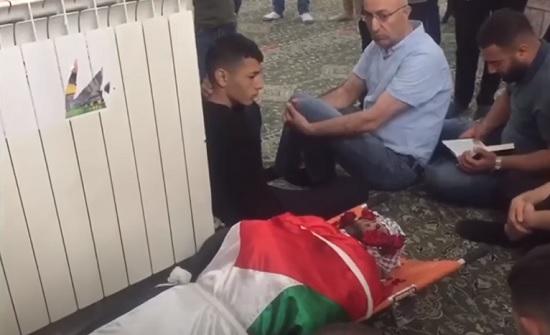 """شاهد :  بقبلات وكلمة """"يا حبيبي"""".. والدة تودع جثمان ابنها الشهيد في رام الله"""