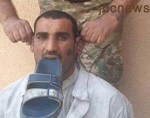صورة : الحشد الشيعي يجبر هذا السني على وضع الحذاء بفمه