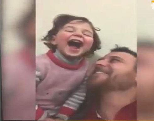 بالفيديو : أب سوري يدرب ابنته على صوت القذائف بطريقة ساخرة