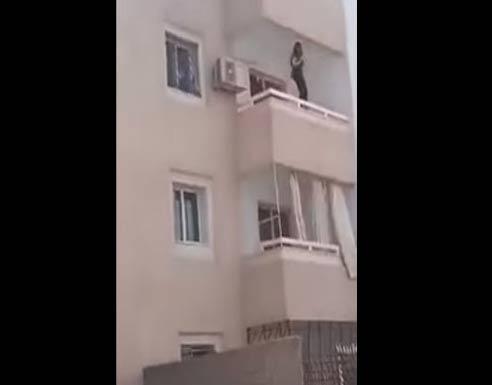 شاهد بالفيديو : الأمن يقنع فتاة بعدم الإنتحار من شرفة عمارة في العقبة
