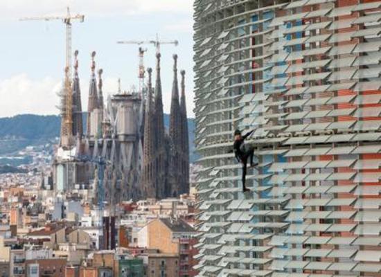 بالفيديو: الرجل العنكبوت يتسلق ناطحة سحاب في برشلونة دون معدات