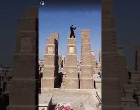 بالفيديو.. عراقي في حالة سكر ينفخ البوق في مقبرة النجف لايقاظ الموتى